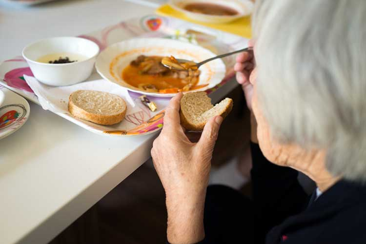 old woman in aged care facility eating a meal