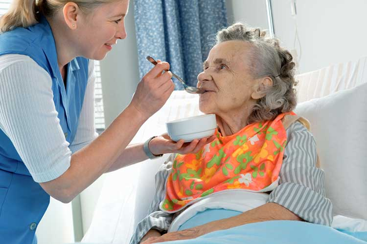 old woman in aged care facility needs meal assistance