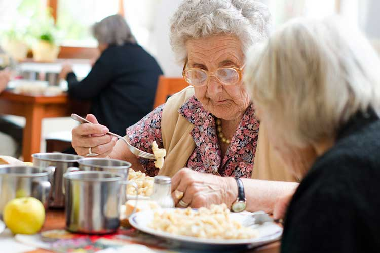 old woman in aged care facility requires meal assistance