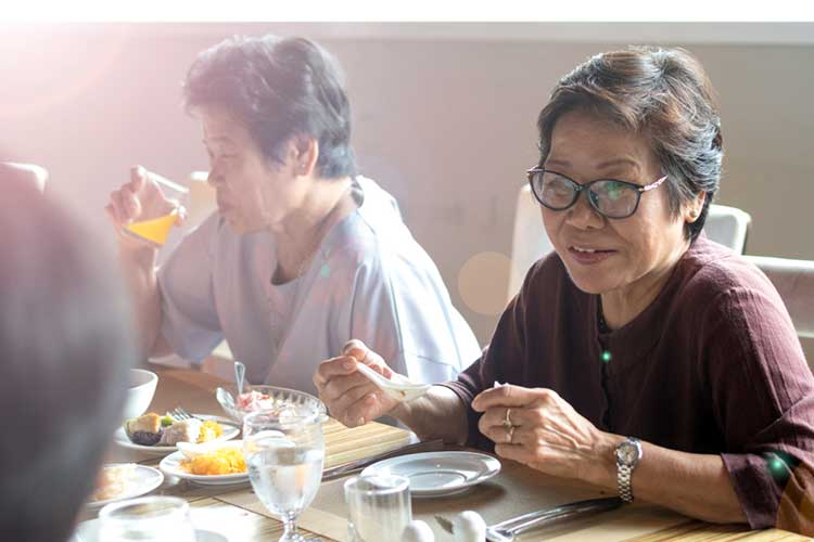 woman eats with friends in aged care facility