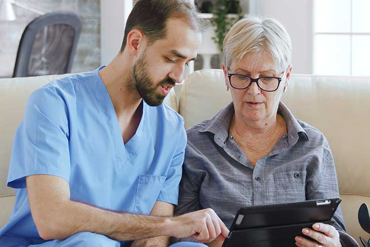 carer showing information to participant on tablet